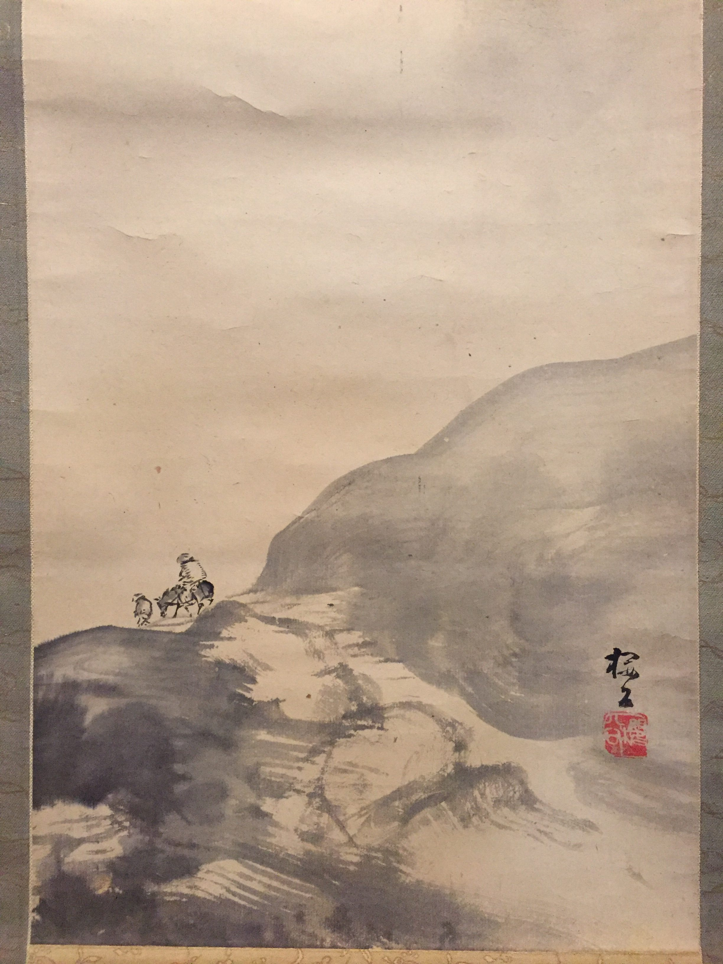 A figure crosses over a hill on a horse pulled by a servant, with Mt. Fuji appearing above the clouds in the background. This work, painted only in black, expresses a sense of perspective through using shades of just that one colour.