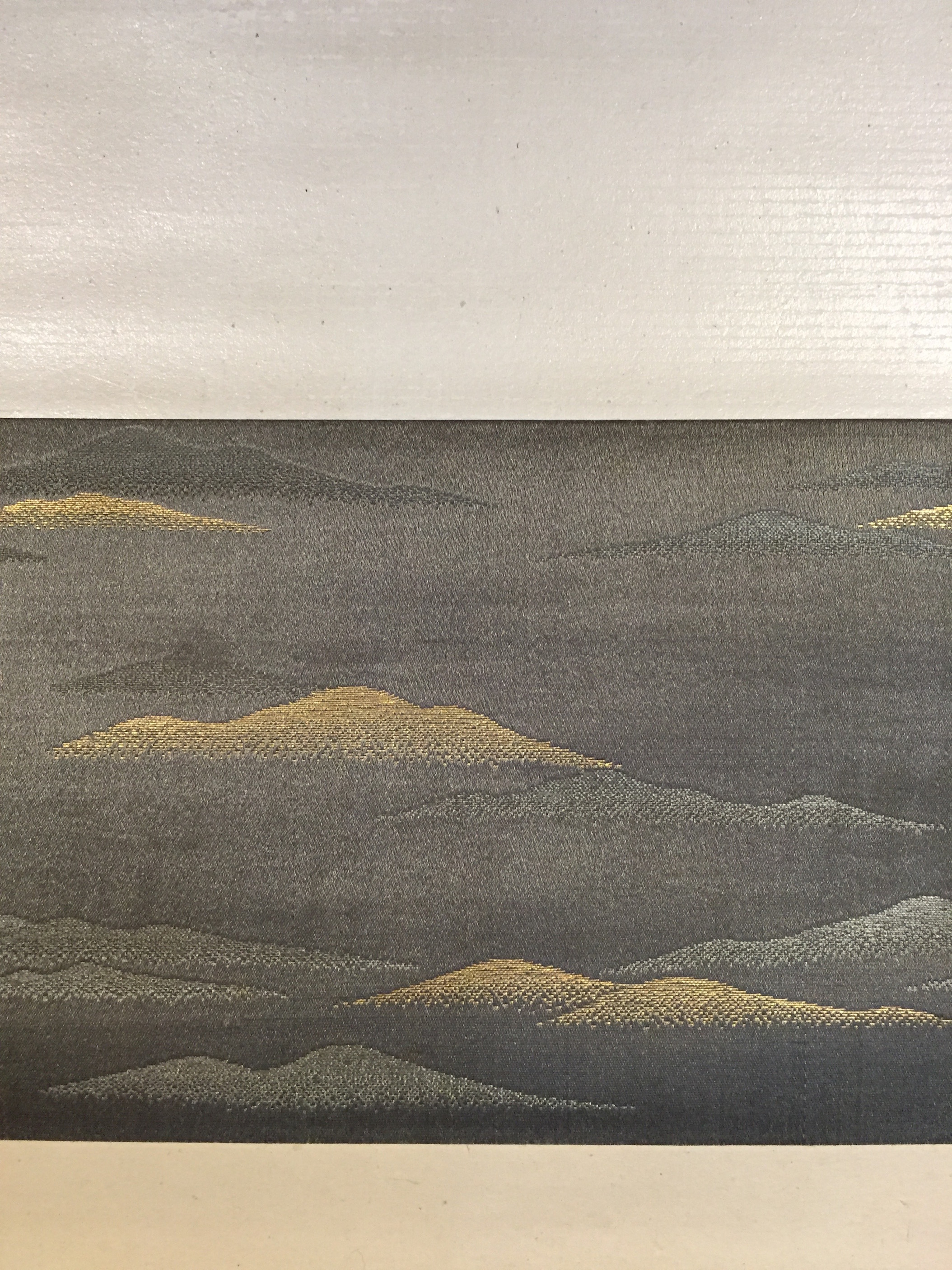 The mounting, in a neutral hue, includes a strip of mountain-patterned fabric in gold and silver around the artwork, making one imagine that the waterfall is deep in the mountains.